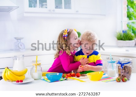 Little girl and boy preparing breakfast in white kitchen. Healthy food for children. Child drinking milk and eating fruit. Happy smiling preschooler kids enjoy morning meal, cereal, banana and berry. - stock photo
