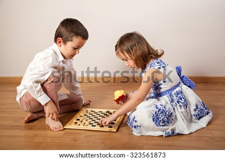 Little girl and boy sitting on the floor and playing chess - stock photo