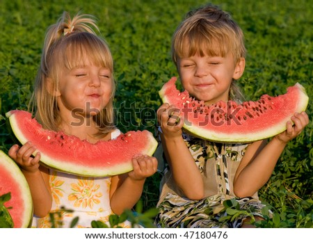 Little girl and boy with a piece of watermelon in hands - stock photo