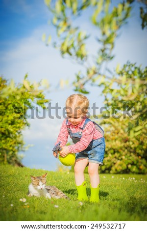 Little Girl and cat play on a green meadow in spring beautiful day - stock photo
