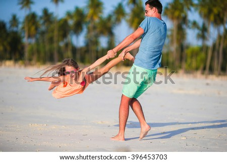 Little girl and dad during tropical beach vacation - stock photo