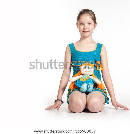 little girl and doll. Good for borders of articles or websites. Beautiful caucasian model. Isolated on white background. cute little girl with a doll  - stock photo