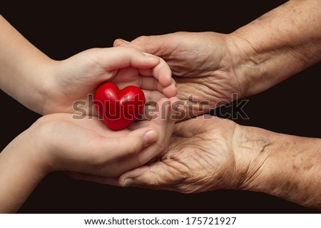 little girl and elderly woman keeping red heart in their palms together, symbol of care and love - stock photo