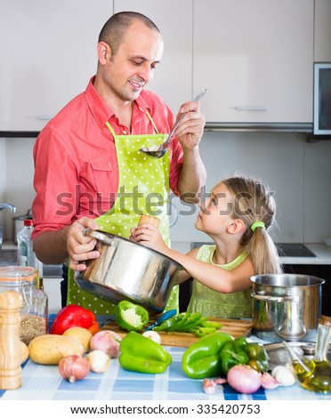 Little girl and  father preparing dinner indoors - stock photo