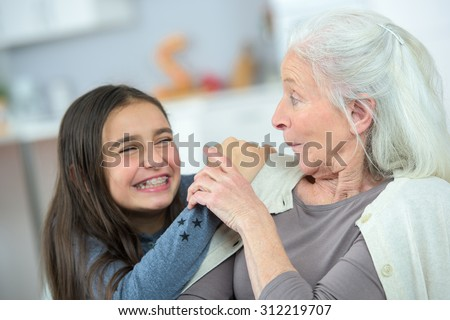 Little girl and grandma whispering secrets - stock photo