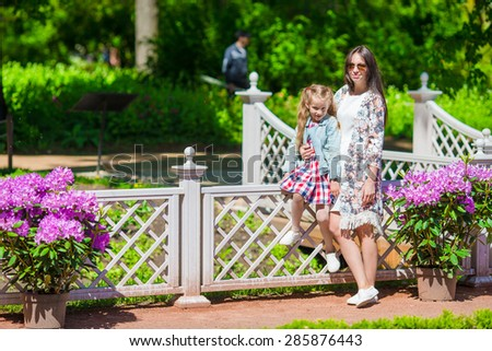 Little girl and happy mom enjoying warm day in tulip garden - stock photo
