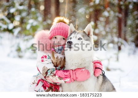 little girl and hasky dog together in winter park - stock photo