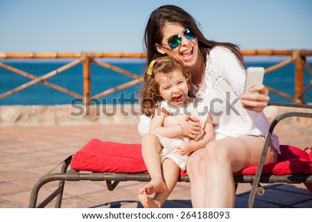 Little girl and her mom having some fun at the beach and taking a selfie with a smartphone - stock photo
