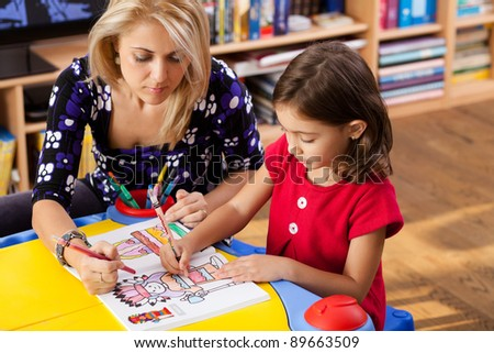 little girl and her mother drawing on a book at playtable - stock photo