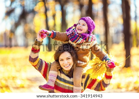 Little girl and her mother playing in the autumn park - stock photo