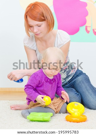 Little girl and her mother playing with pyramid. - stock photo