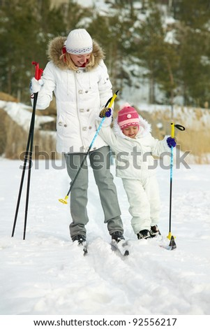 Little girl and her mother skiing in park - stock photo