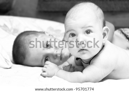 Little girl and her toddler brother are lying on a bed. Black  and white photo - stock photo
