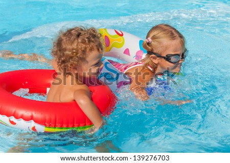 little girl and little boy playing in the pool with rubber rings - stock photo