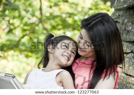 Little girl and mother enjoy tablet PC in park. - stock photo
