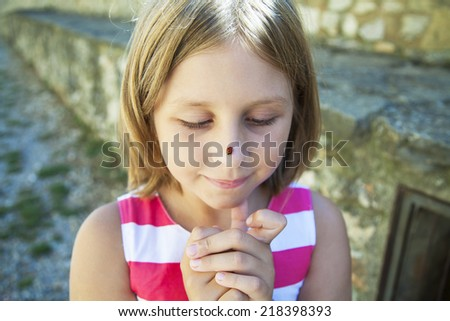 Little girl and the ladybird sits - stock photo