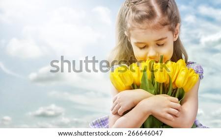little girl and yellow tulips - stock photo