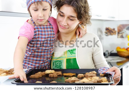 Little girl and young mother with baked cookies - stock photo