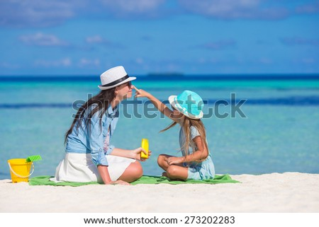 Little girl applying sun cream to her mother nose - stock photo