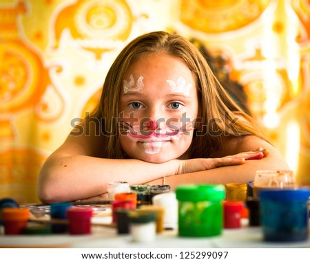 Little girl artist, drawing paint with paint of face. - stock photo
