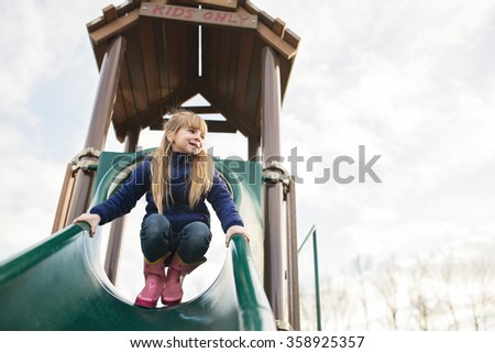 Little girl  at the top of a playground slide - stock photo