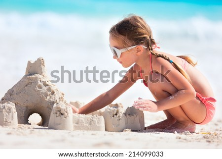 Little girl at tropical beach making sand castle - stock photo