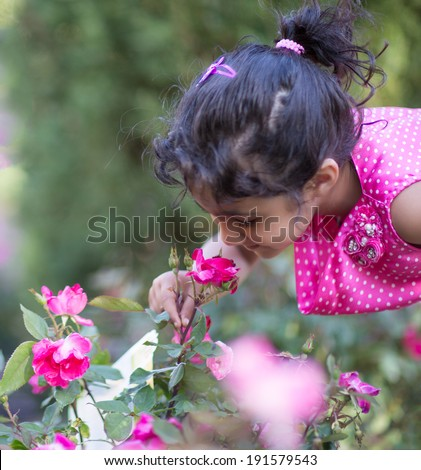 Little Girl Attempting to Smell a Rose in the Garden - stock photo