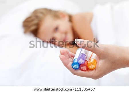 Little girl awaiting homeopathic medication - hand with bottles in foreground - stock photo