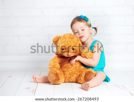 little girl baby hugging a loved teddy bear - stock photo
