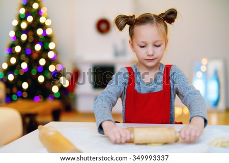 Little girl baking Christmas cookies at home on Xmas eve. Beautifully decorated room, fireplace, Christmas tree and lights on background. - stock photo