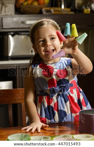 Little Girl Baking Cookies. Beautiful daughter playing with pastry utensils helping her mother to prepare muffins - stock photo