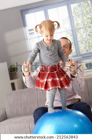 Little girl balancing on fit ball at home in living room, father helping by holding hands. - stock photo