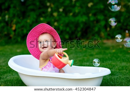 little girl bathes in a bath with soap bubbles - stock photo