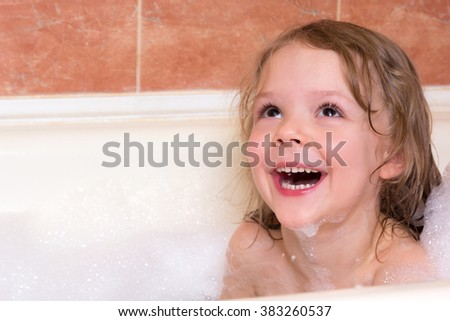 little girl bathes in the bathtub with foam - stock photo