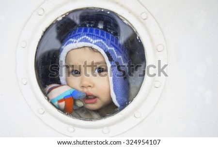 little girl behind the ship window - stock photo