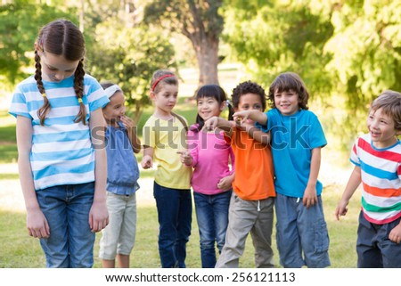 Little girl being bullied in park on a sunny day - stock photo