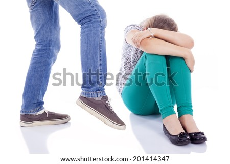 Little girl being kicked by a boy, isolated on white background - stock photo
