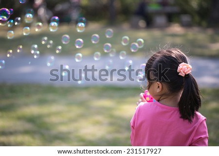 Little girl blowing bubbles under the sun - stock photo
