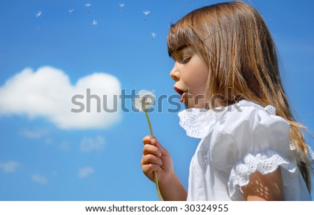 Little girl blowing dandelion, blue sky and heart shape cloud in the background - stock photo