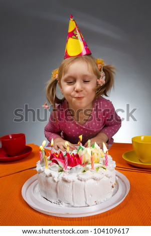 Little girl blowing out candles in her birthday (Focus is on cake) - stock photo
