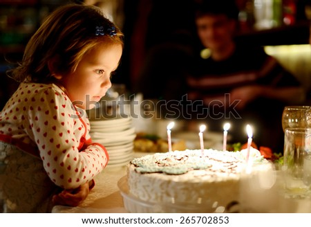 Little girl blowing out candles in her birthday (shallow focus) - stock photo