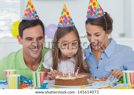 Little girl blowing out her candles with her parents - stock photo