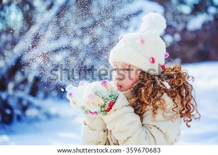 Little girl blows snow with mittens, on a snowflakes bokeh background. - stock photo