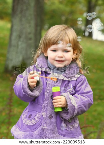 Little girl blows soap bubbles in the park on natural background - stock photo