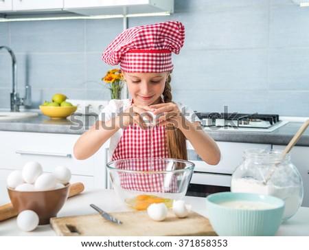 little girl breaking eggs into a glass bowl preparing a dough - stock photo