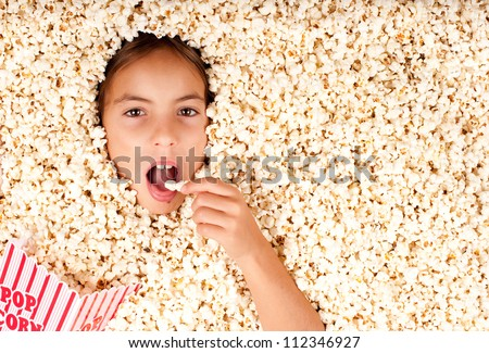 little girl buried in popcorn - stock photo