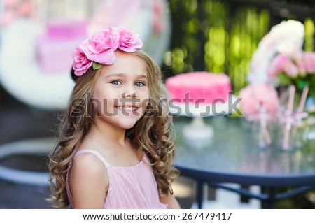 Little girl celebrate Happy Birthday Party with rose decor in the beautiful garden - stock photo