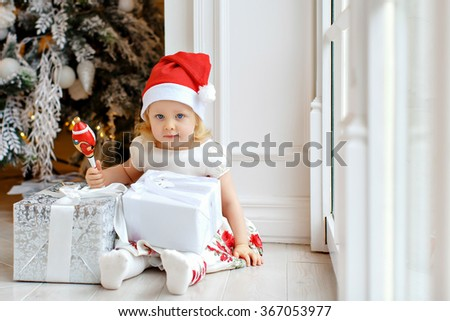 Little girl charming blonde in a Santa hat, smiling and sitting on the floor against the backdrop of the Christmas tree in the interior of the house - stock photo