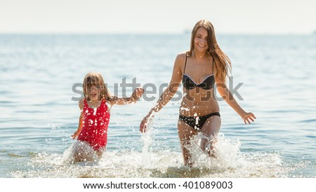 Little girl child and mother running having fun in ocean. Kid and woman bathing in sea splashing water. Summer vacation holiday relax. - stock photo