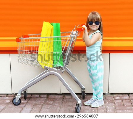 Little girl child and shopping cart with bags against the colorful orange wall - stock photo